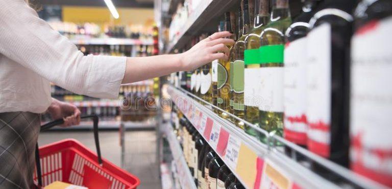 la-mano-toma-una-botella-de-vino-del-estante-en-el-supermercado-compra-departamento-alcohol-tienda-mujer-concepto-muchacha-140984480